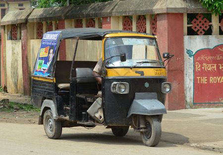 autorick: KOLKATA, INDIA - JUL 8, 2015. Private auto rickshaw three-weeler tuk-tuk taxi drives down the street in Kolkata. Indian three-wheelers have the design of the Piaggio Ape C, from 1948.