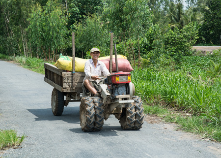 adult vietnam: Can Tho, Vietnam - Oct 12, 2015. A man riding farm vehicle in Can Tho, Vietnam. Mekong Delta is by far Vietnams most productive region in agriculture.