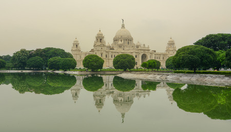 west bengal: View of the Victoria Memorial and its reflection in the water feature in the foreground. Built by the British during colonial times it is a prominent feature in Kolkata.