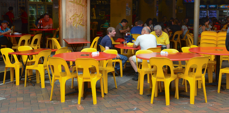 go inside: SINGAPORE - MAY 5, 2015. People eat at a popular food hall in Chinatown, Singapore. Inexpensive food stalls are numerous in the city so most Singaporeans dine out at least once a day.