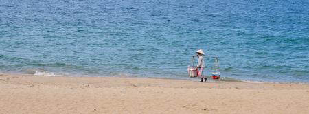 trang: Nha Trang, Vietnam - Oct 10, 2015. A vendor walking on Nha Trang beach. Nha Trang is a coastal city in Vietnam, famous with beautiful beaches and bays. Editorial