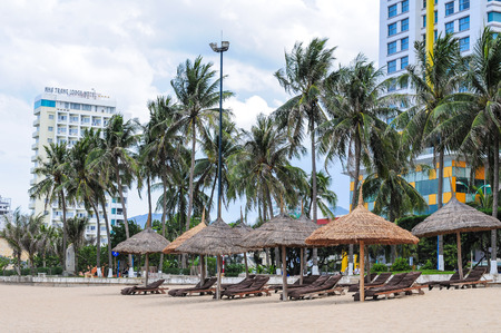 coastal city: Many chairs with umbrellas on the Nha Trang beach. Nha Trang is a coastal city in Vietnam, famous with beautiful beaches and bays.