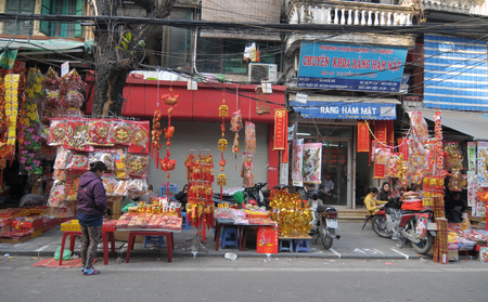 important people: HANOI, VIETNAM - FEB 3, 2015. Vietnamese people sell Tet decorations on the street in Hanoi, Vietnam. Tet is the most important holidays of the people of Vietnam.