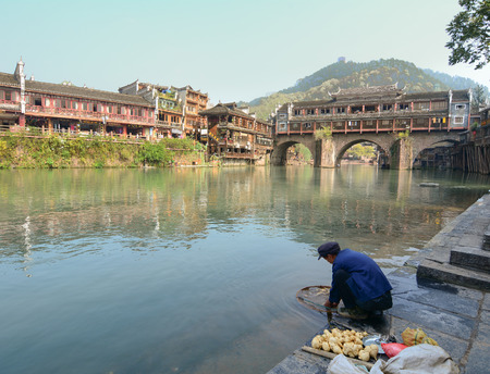 tentative: HUNAN, CHINA - OCT 22, 2015. A man washing foods on riverbank at Fenghuang county in Hunan, China. The ancient town of Fenghuang was added to the UNESCO World Heritage Tentative List in the Cultural category.