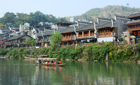 tentative: HUNAN, CHINA - OCT 22, 2015. Tourists on the wooden boat at Fenghuang county in Hunan, China. The ancient town of Fenghuang ,Tentative List in the Cultural category. Editorial