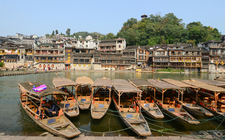 tentative: HUNAN, CHINA - OCT 22, 2015. Many boats docking on tourist pier at Fenghuang county in Hunan, China. The ancient town of Fenghuang Tentative List in the Cultural category. Editorial