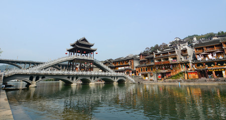 tentative: HUNAN, CHINA - OCT 22, 2015. Old houses and bridge located at Fenghuang county in Hunan, China. The ancient town of Fenghuang was added to the UNESCO World Heritage Tentative List in the Cultural category. Editorial