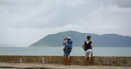 con dao: Con Dao, Vietnam - Oct 22, 2015. Young men standing and seeing the sea at Con Dao island, Vietnam.