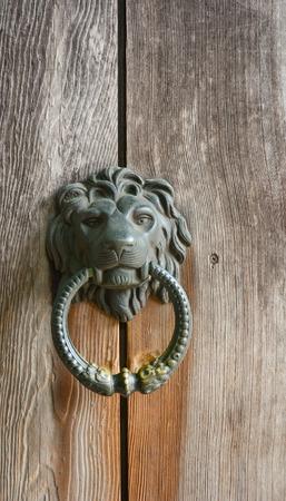 door knob: Decorative gilded lion head door knob on wooden background. Detail from the streets of Prague.