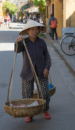 hoi an: Hoi An, Vietnam - Nov 3, 2015. An old woman in traditional Vietnamese clothes carrying buskets with food on the street in Hoi An Ancient Town, Vietnam.