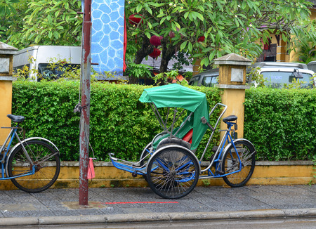hoi an: HOI AN, VIETNAM - NOV 14, 2015. Cyclo parked on the side street at Hoi An, Vietnam. Hoi An is a tourist attraction because of its history, traditional architecture and crafts such as textiles and ceramics.