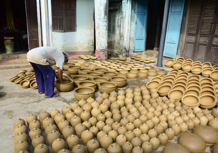out of production: Hoi An, Vietnam - October 25, 2015. A man working in pottery production base in Hoi An, Vietnam. They used clay to shape by hand out flower pots.
