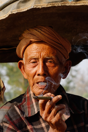 cheroot: Yangon, Myanmar - Feb 22, 2016. Old man smoking Burmese cheroot cigar on one of the hottest recorded days before monsoon season in Yangon, Myanmar.