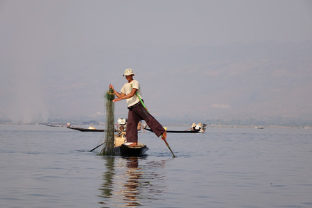 Inle, Myanmar - Feb 15, 2016. Traditional Burmese fishermen with fishing net at Inle lake in Myanmar. Inle is the second largest lake in Myanmar with an estimated surface area of 44.9 square miles.
