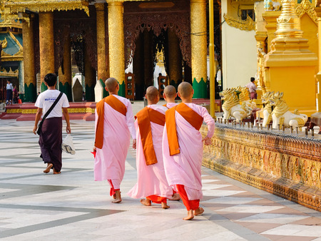 Yangon, Myanmar - Feb 26, 2016. Nuns walking at Shwedagon pagoda at sunny day in Yangon, Myanmar.
