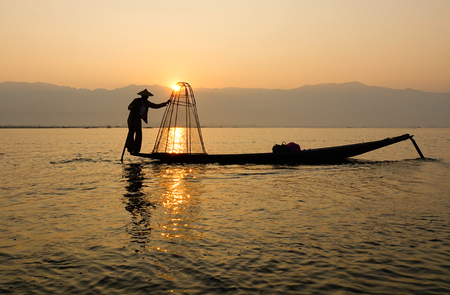 Burmese man with fishing net at sunrise in Inle lake, Myanmar. Inle is the second largest lake in Myanmar with an estimated surface area of 44.9 square miles.