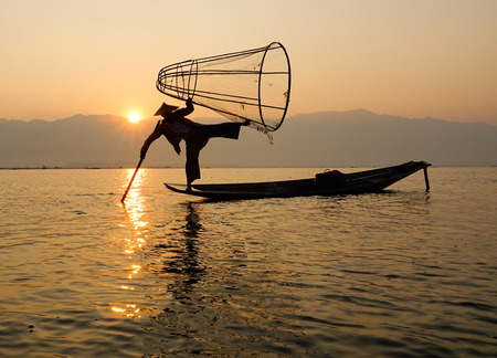 A man catching fish on Inle lake in Myanmar. Inle is the second largest lake in Myanmar with an estimated surface area of 44.9 square miles. Stock Photo