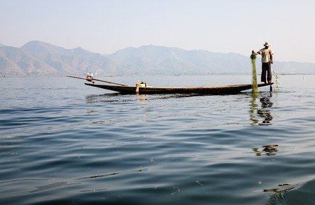 Burmese man catching fish on Inle lake in Myanmar. Inle is the second largest lake in Myanmar with an estimated surface area of 44.9 square miles.