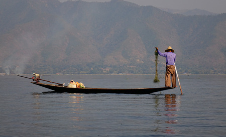 Burmese man with fishing net at Inle lake in Shan, Myanmar. Inle is the second largest lake in Myanmar with an estimated surface area of 44.9 square miles.