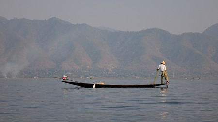 Burmese man rowing boat on Inle lake in Myanmar. Inle is the second largest lake in Myanmar with an estimated surface area of 44.9 square miles.