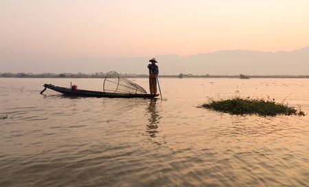 Burmese people with fishing net at sunrise on Inle lake in Myanmar. Inle is the second largest lake in Myanmar with an estimated surface area of 44.9 square miles.