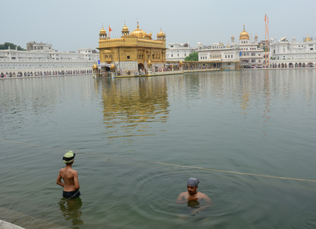 Amritsar, India - Jul 25, 2015. Sikh people bathing on the holy lake at Golden Temple in Amritsar, India. Editorial