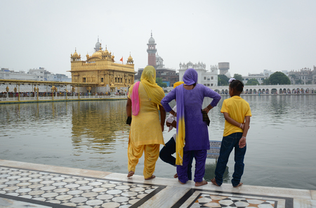 holiest: Amritsar, India - Jul 25, 2015. A Sikh family standing and seeing the Golden Temple in Amritsar, India. Golden Temple is the holiest Gurdwara of Sikhism.
