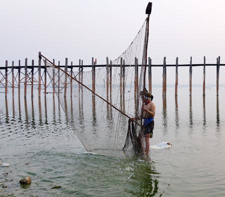 Mandalay, Myanmar - Feb 21, 2016. A Burmese man catching fish on lake near Ubein bridge in Mandalay, Myanmar. Editorial