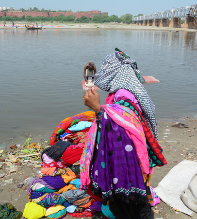 Agra, India - Jul 13, 2015. A woman carrying and drying cloth on the sandy banks of Yamuna river, Agra, India.
