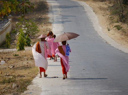 Yangon, Myanmar - Feb 21, 2016. Buddhist nuns walking for morning alms on rural road in Yangon, Myanmar. Yangon is the largest city in Myanmar (formerly Burma).