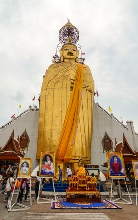 BANGKOK, THAILAND - JUL 30, 2015. Giant Golden Buddha statue with portraits of Thai Royal Family at Wat Mahathat in Bangkok, Thailand.