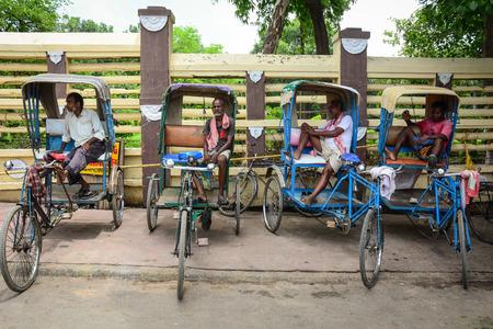 bodhgaya: Bodhgaya, India - Jul 9, 2015. Indian men with rickshaw waiting for passengers on street in Bodhgaya, India.