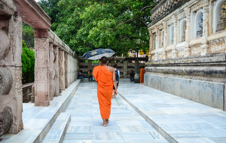 banian: Bodhgaya, India - Jul 9, 2016. A Buddhist monk - like many people from all over the world - is circling Mahabodhi Temple in Bodhgaya, India. Editorial