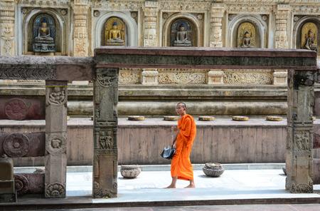 banian tree: Bodhgaya, India - Jul 9, 2016. Buddhist monk - like many people from all over the world - is circling Mahabodhi Temple in Bodhgaya, India.