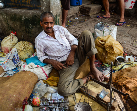 bodhgaya: Bodhgaya, India - Jul 9, 2015. Unidentified man sitting in a crowded market in Bodhgaya, India. Its a common practice in India to sell vegetables in open markets and streets.