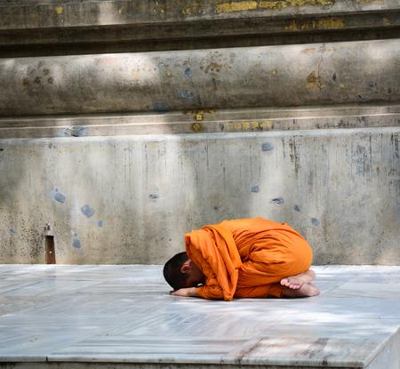 bodhgaya: Bodhgaya, India - Jul 9, 2016. A young monk praying on his knees at Mahabodhi Temple in Bodhgaya, India.