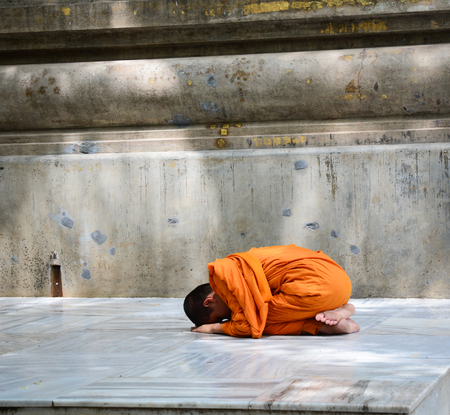 Bodhgaya, India - Jul 9, 2016. A young monk praying on his knees at Mahabodhi Temple in Bodhgaya, India.