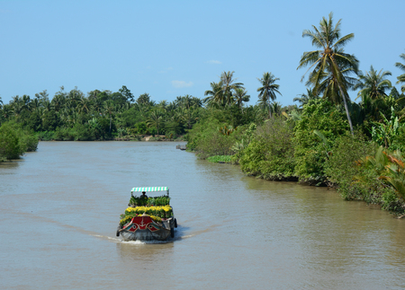 can tho: A cargo boat running on the Mekong river at sunny day in Mekong Delta, southern Vietnam.