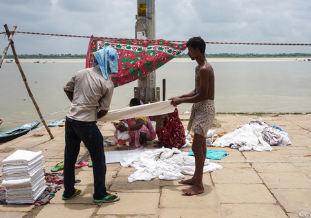 pilgrim journey: Varanasi, India - Jul 12, 2015. Indian men doing their daily activities by the River Ganga at the Assi Ghat, including drying their clothes. Ghats of Varanasi serves many purposes. Editorial