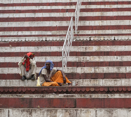 Varanasi, India - Jul 12, 2015. People sitting and praying on the ghat in Varanasi, India. Varanasi is a holy Indian city of the banks of the Ganga in Uttra Pradesh, India.