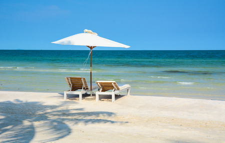 Idyllic tropical beach with relaxing chais and umbrella in sunny day at summer