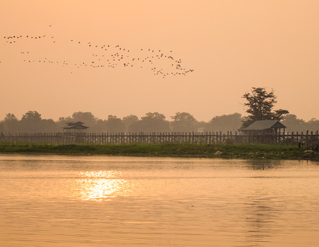 Ubein bridge with birds in Mandalay, Myanmar. Ubein was built around 1850 and is believed to be the oldest and longest teakwood bridge in the world. Stock Photo