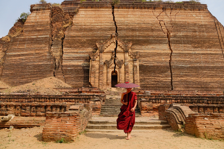 A Buddhist monk in the red robe with umbrella at the acient pagoda in Myanmar. Stock Photo