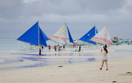 Boracay, Philippines - Dec 17, 2015. Tourists relax on White beach in Boracay, Philippines. Boracay Island has received awards from numerous travel publications and agencies.