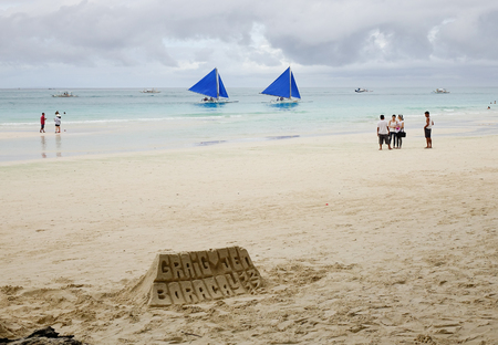 publications: Boracay, Philippines - Dec 17, 2015. People on White beach with sand castles in Boracay, Philippines. Boracay Island has received awards from numerous travel publications and agencies.