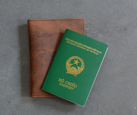 identity card: Vietnamese passport with a wallet on the stone floor. Closed-up.