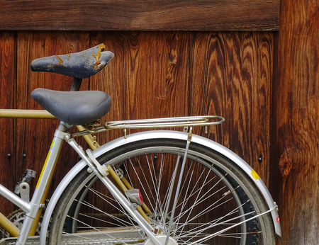 Old bike against the wooden wall of old house in Asia. Stock Photo