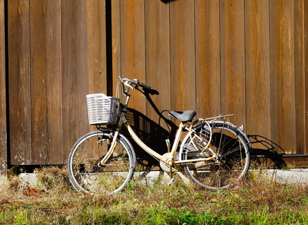 Vintage bicycle on vintage wooden house wall in the sunny day.