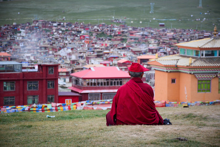 A Tibetan monk sitting on the hill at sunset in Yarchen Gar, Sichuan, China. Yarchen Gar is the largest concentration of nuns and monks in the world.