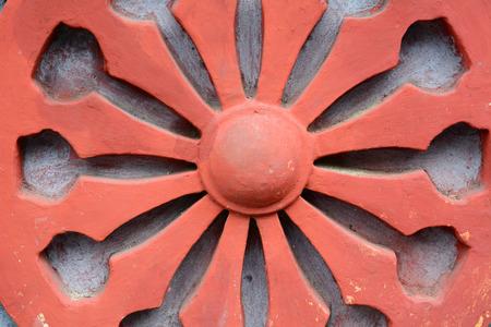 Dharma Wheel Buddhist symbol in old door of local temple in Vietnam.
